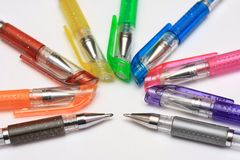 Colored pens, gray background, radial shape. Colored pens on light gray background. Photo of different color pens aligned in a radial shape. Concept photo of Stock Photo