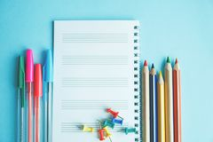 Colored pens and magnifier on a white sheet of notepad for text.Education or business concept stock image