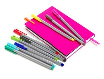 Colored pens on a notebook. Back to school supplies. Isolated on white background royalty free stock photography