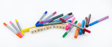 Colored pens with wooden cubes that form the words - drawing time on a white background Stock Photo