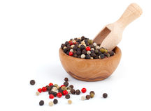 Colored Pepper. In the wooden bowl, on the white background Royalty Free Stock Photo