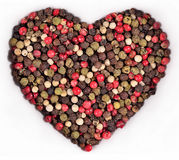 Colored pepper in the form of heart on a white Royalty Free Stock Image