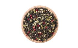 Colored pepper peppercorns in wooden bowl isolated on white background. Spices and food ingredients royalty free stock image