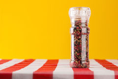 Colored Peppers Mix and pepper mill on tablecloth Royalty Free Stock Photos