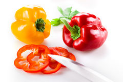Colored peppers with slice on white background Stock Photos