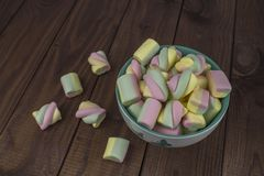 Colored pieces of marshmallow spiral in a plate on a dark wooden table. Sweet rainbow colored candies, marshmallow, aerial dessert. Colored pieces of marshmallow royalty free stock photos