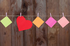 Colored pieces of paper and heart hanging on a rope Royalty Free Stock Image