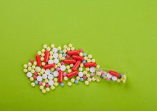 Colored pills. Colored vitamins on green paper Stock Photo