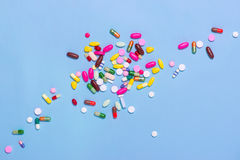 Colored pills on blue background. Royalty Free Stock Images