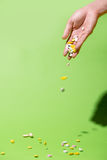 Colored pills falling from hand on green background. Stock Image