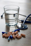 Colored pills with a glass of water. And stethoscope Stock Image