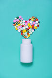 Colored pills in heart shape with bottle  on blue background. Stock Photos