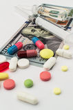 Colored pills with money. Health costs a lot Royalty Free Stock Photos