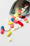 Colored pills with money. Health costs a lot Stock Photography