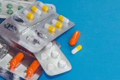 Colored pills, tablets and capsules on a blue background stock photo