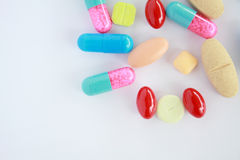 Colored pills, tablets and capsules on a white Royalty Free Stock Image