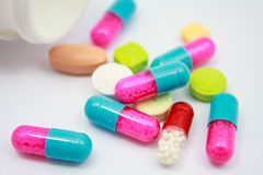 Colored pills, tablets and capsules on white Stock Images