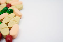 Colored pills, tablets and capsules on a white Royalty Free Stock Photo