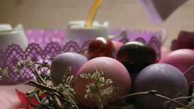 A colored pink Easter egg lies on the background of a tea poured in the cup stock video footage