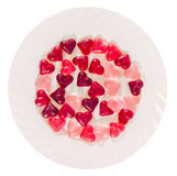 Colored (pink, red and orange), transparent heart shape jellies with ceramic plate,  Royalty Free Stock Photography