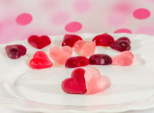 Colored (pink, red and orange), transparent heart shape jellies with ceramic plate, colored degradee texture background Stock Photo