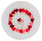 Colored (pink, red and orange), transparent heart shape jellies with ceramic plate, white background Stock Photos