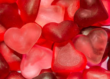 Colored (pink, red and orange), transparent heart shape jellies, colored degradee background Stock Photos