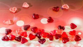 Colored (pink, red and orange), transparent heart shape jellies, colored degradee background Stock Images