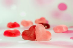 Colored (pink, red and orange), transparent heart shape jellies, colored degradee background Royalty Free Stock Image