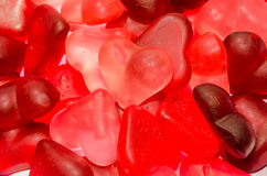 Colored (pink, red and orange), transparent heart shape jellies, colored degradee background Royalty Free Stock Photos