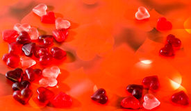 Colored (pink, red and orange), transparent heart shape jellies, red heart light background Royalty Free Stock Photo