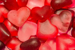 Colored (pink, red and orange), transparent heart shape jellies, texture background Royalty Free Stock Image