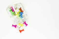Colored pins. Glass bin, white background royalty free stock photo