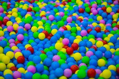 Colored plastic balls in pool of game room. Swimming pool for fun and jumping in colored plastic balls Royalty Free Stock Photography