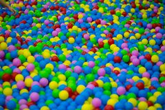 Colored plastic balls in pool of game room. Swimming pool for fun and jumping in colored plastic balls Stock Image