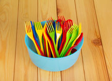 Colored plastic bowl, fork and spoon on  background  light wood. Stock Photo
