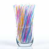 Colored plastic drinking straws. In clear glass on a white background Stock Photography