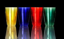 Colored plastic glasses on black Royalty Free Stock Photos