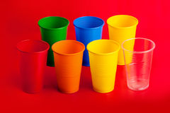 Colored plastic glasses on red background Royalty Free Stock Photos