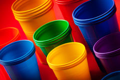 Colored plastic glasses on red background. Studio shoot stock images