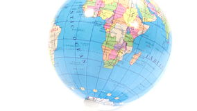 Colored plastic globe. Tilt from white background over Africa to white background stock footage