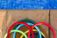 Colored plastic rings on the mosaic of the edge of a swimming po. Zenital view of colored plastic rings on the mosaic of the edge of a swimming pool stock images