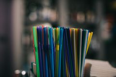 Colored Plastic Straws For Drinking On Blurred Background Stock Photos
