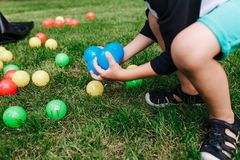 Colored plastic toy balls spilled in the grass. Boy gethering blue balls. Baby birthday party activity royalty free stock photos
