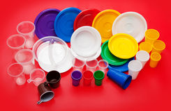 Colored plastic utensils on red background Royalty Free Stock Photography