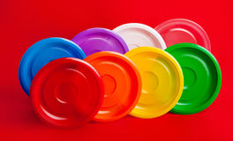Colored plastic utensils on red background Stock Images