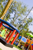 Colored Playground. Playground swing close up in red and blue Royalty Free Stock Photography