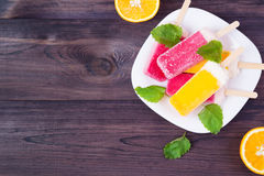 Colored popsicles. On a plate with melissa and oranges on the wooden background royalty free stock photo
