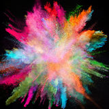 Colored powder explosion on black background. Stock Photos