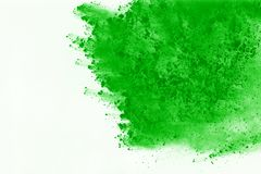Colored powder explosion. Colore dust splatted. Freeze motion of Green powder exploding on white background royalty free stock photo